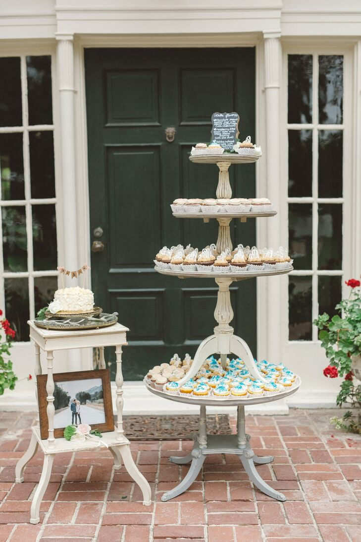 Wooden tables stacked on top of one another displayed an assortment of delicious-looking cupcakes. The single-tiered rosette wedding cake sat on top of a single wooden table, decorated with a flag topper that read Christy and Brady's monogram.