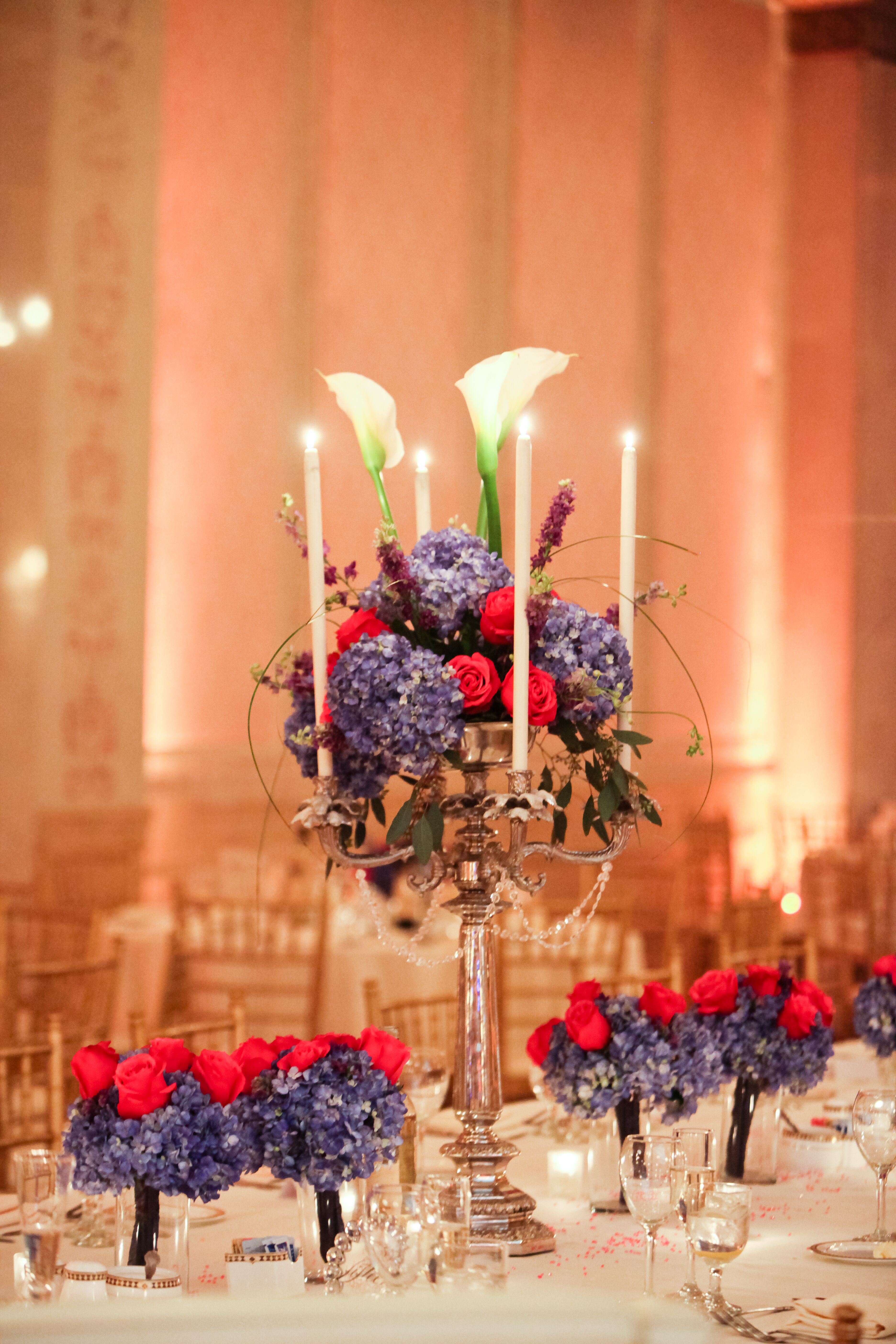 Tall candelabra centerpieces with red roses blue
