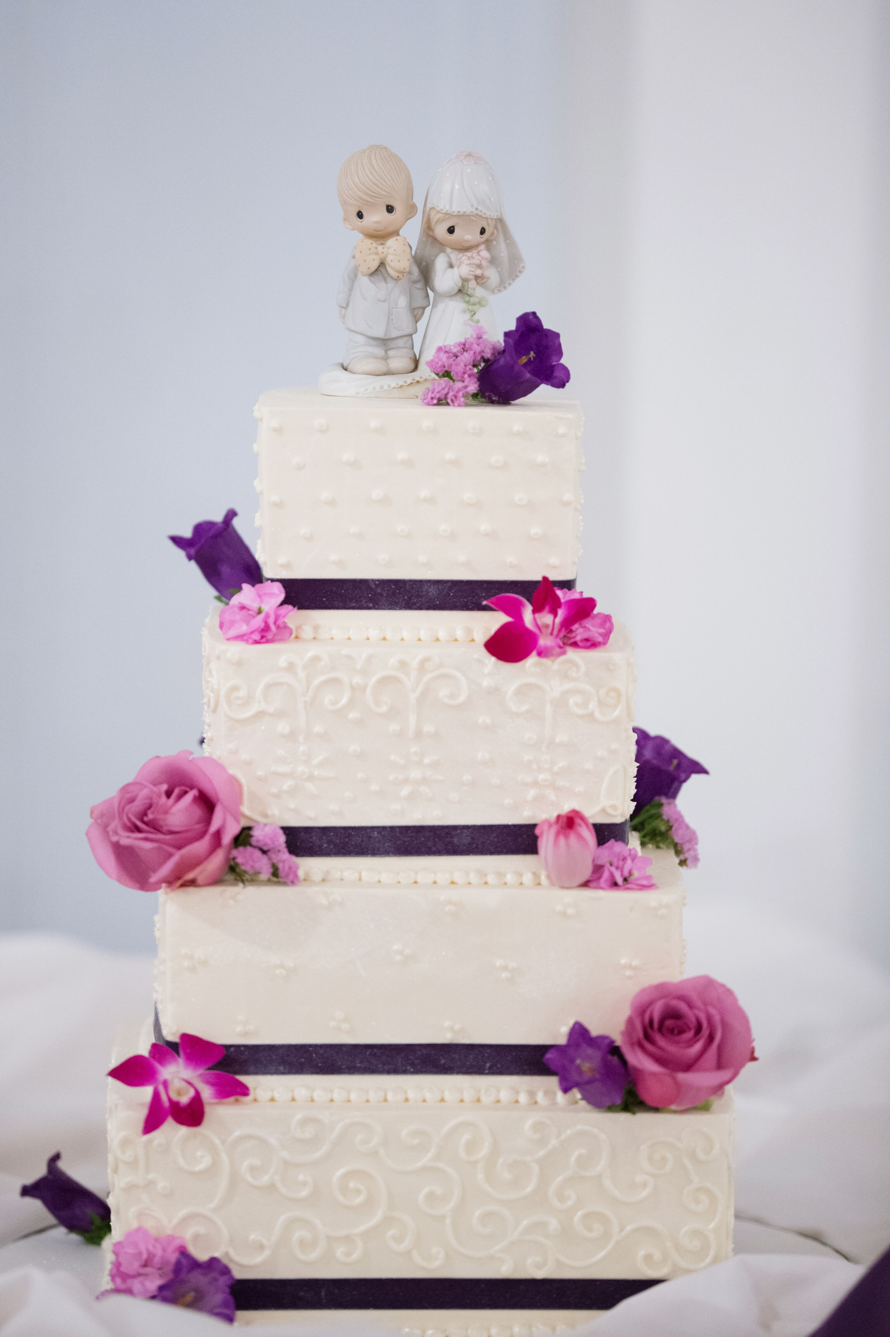 Square Tiered White Cake With Pink And Purple Flowers And