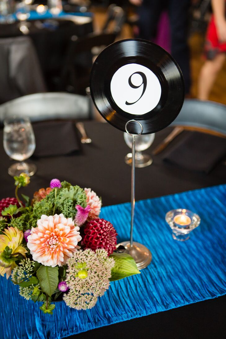 Anna and Brandon's theme for their wedding was music, because it's such a big part of their lives. They had a DJ spin vinyl the whole night, and the table numbers were repurposed 45 rpm records.