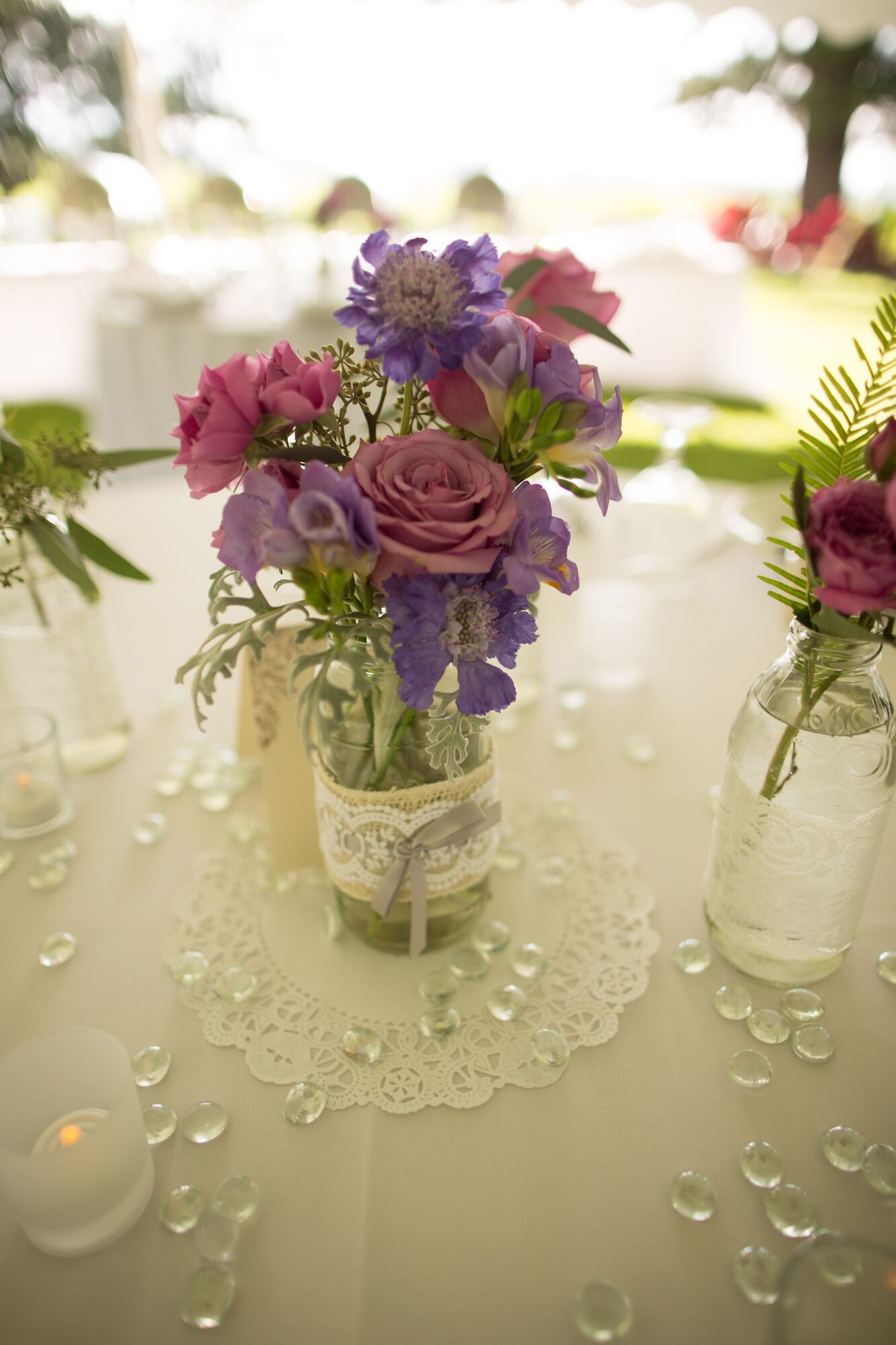 Purple Flowers In Glass Bottle Centerpiece