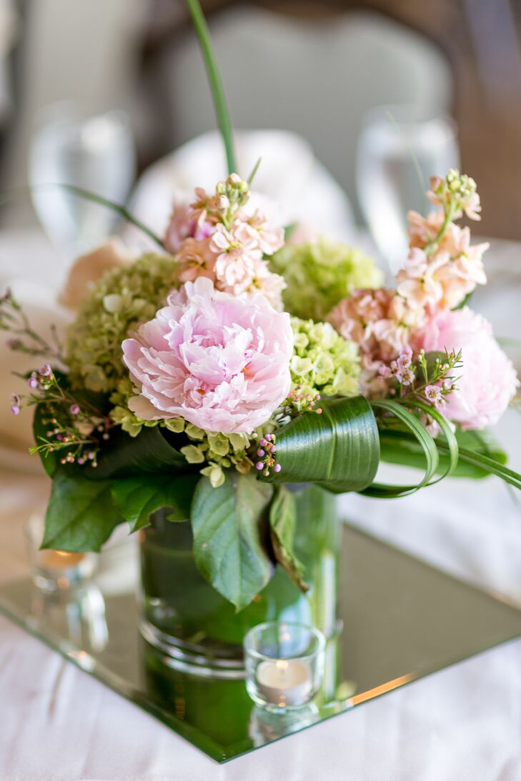 The reception tables were topped with pink peonies and green viburnum on top of square mirrors. Stephanie and Marc loved how the beautiful arrangements, from Palmer Flowers, added plenty of romance to Fort Collins Country Club in Fort Collins, Colorado.