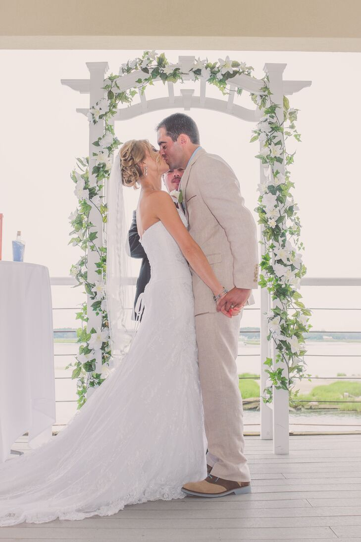 Stephanie and Nate shared their first kiss a the waterfront ceremony under a white wooden arch decorated with imitation white lilies and ivy.