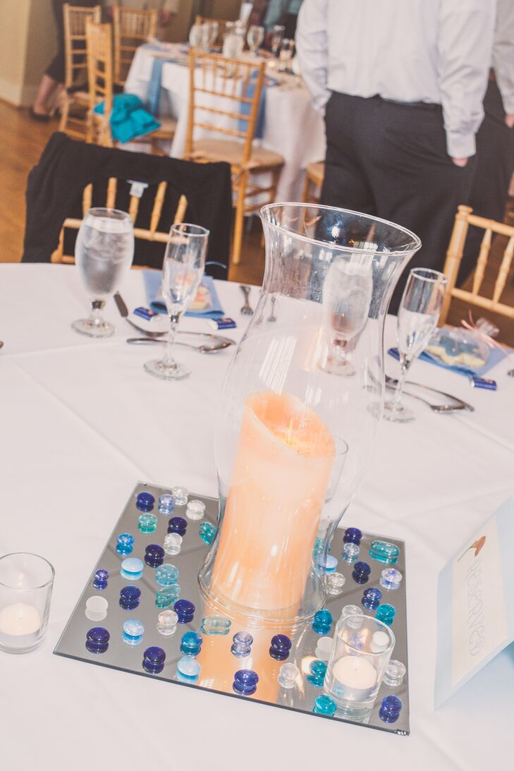 The centerpieces were kept simple, with glass vases filled with peach candles on mirrors covered in blue glass pebbles.
