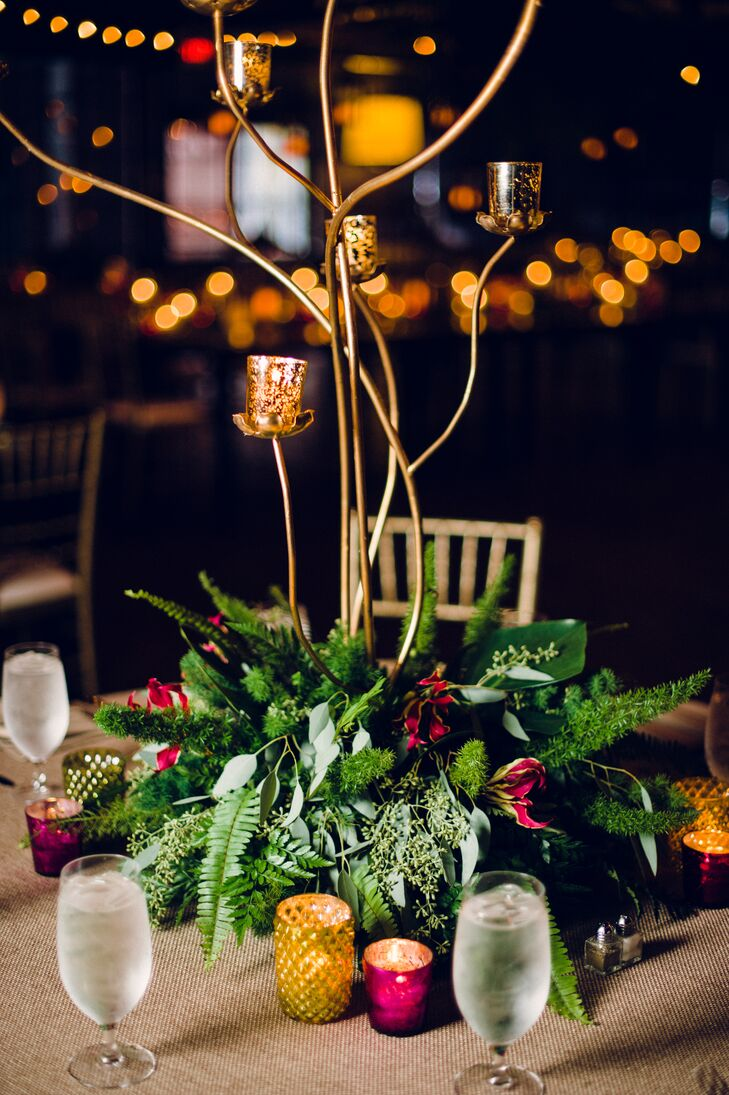 Tropical-inspired arrangements included a lush mix of orchids, flax leaves, lily grass and pin cushion proteas, while a one-of-a-kind chandelier made from giant monstera leaves and date branch clusters hung from the ceiling