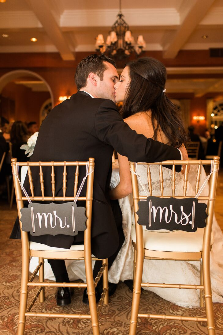 "Of course, with a room covered in gold and white, Mariel and Colin made room for their darkest hue. Together they brought out their black wedding color with dual signs: ""Mr."" and ""Mrs."" in black-and-white marked their gold chiavari chairs at the reception at Ridgewood Country Club in Paramus, New Jersey."