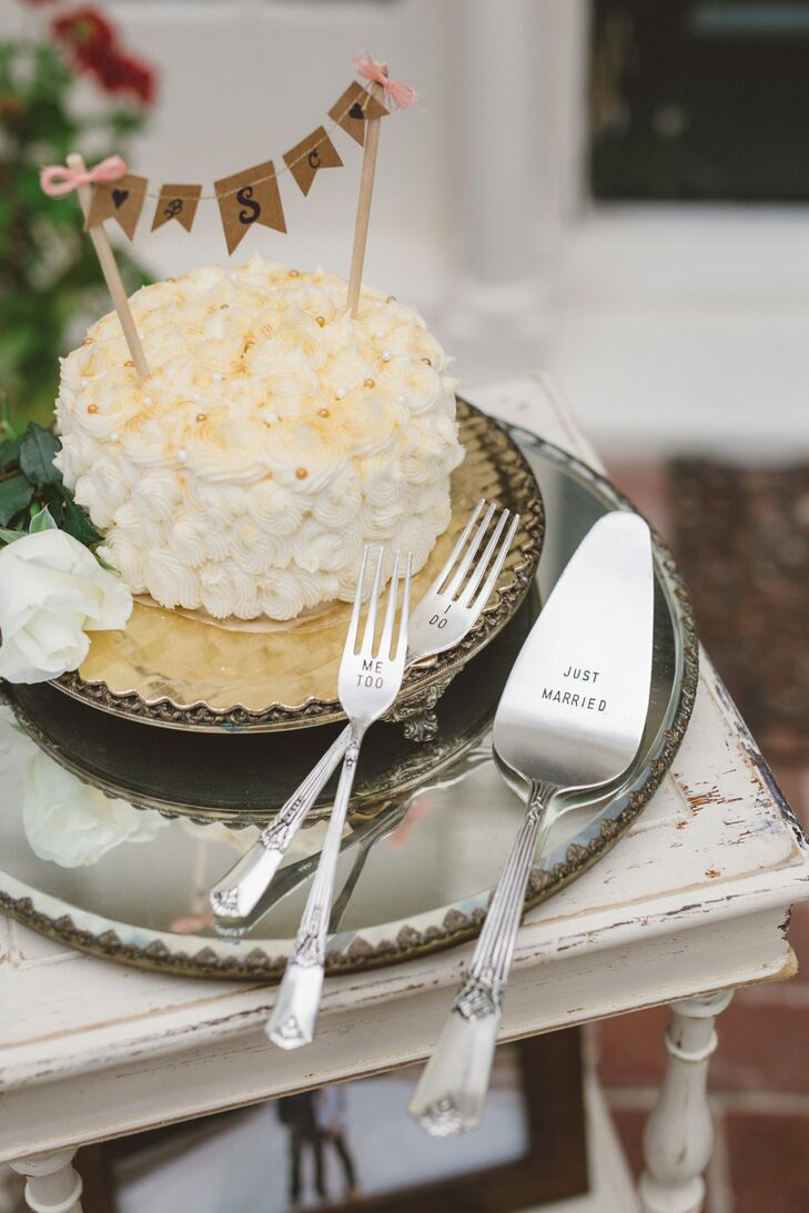 "The small white cake had a rosette pattern and a flag topper that displayed Christy and Brady's monogram. They served the cake with a silver serving set, which had engraved forks that read ""I Do"" and ""Me too"", positioned next to the knife that read ""Just Married."""