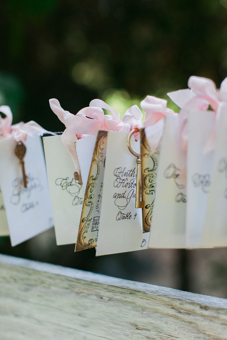 The names and seating assignments of each guest were hand-lettered onto antiqued cardstock embellished with dainty pink bows and vintage skeleton keys.