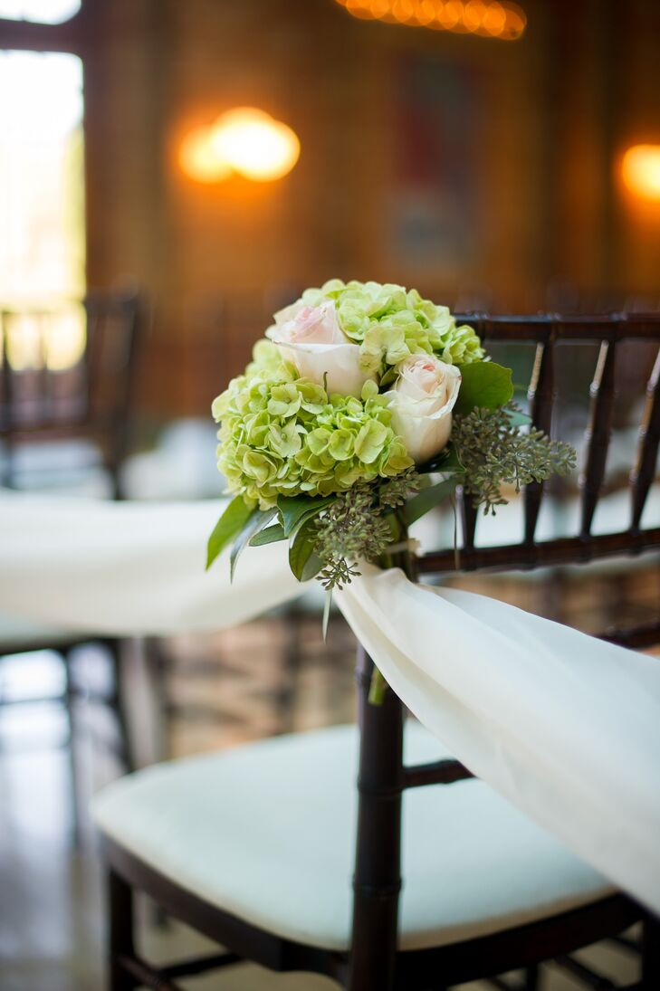 The aisle was lined with petite bunches of neutral blooms to complement the more bold altar arrangements.