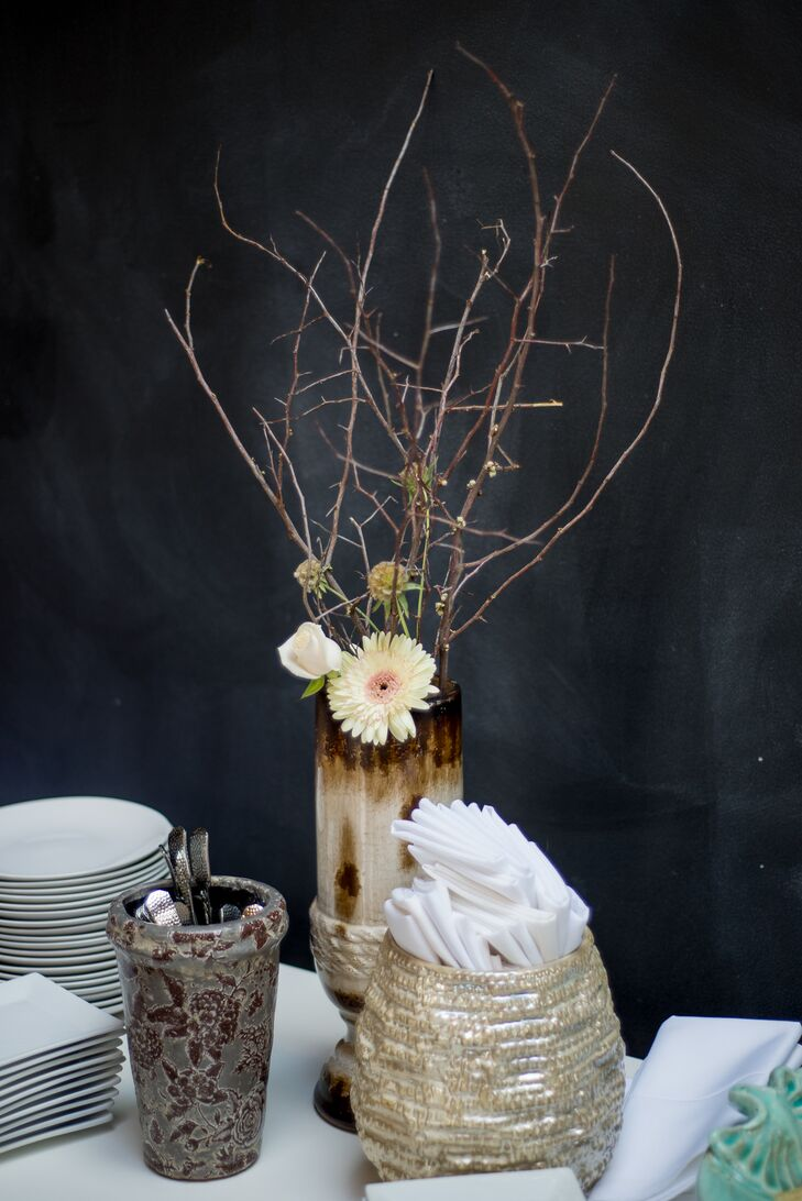 Ivory gerbera daisies with pink centers and scabiosa pods were mixed in with tall branches to create a rustic centerpiece.