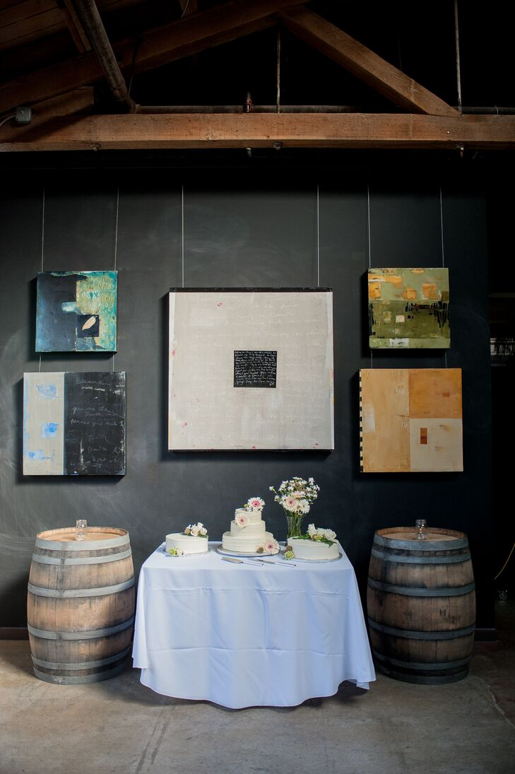 Wood barrels were on either side of the dessert table, with pieces of art decorating the wall.