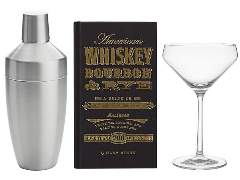 A cocktail shaker, a whiskey, bourbon and rye cocktail recipe book and a cocktail glass next to each other