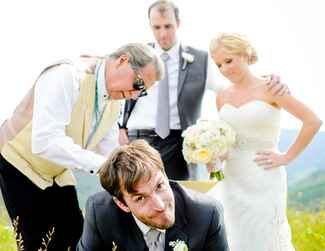 Officiant signs marriage license on the groom's back