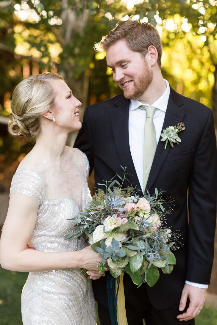 "Sean wore a succulent and rose boutonniere pinned to the lapel of his classic black suit, which he complemented with a white collared dress shirt and a silver tie. ""The men wore boutonnieres of a single succulent and spray rose accented with seeded eucalyptus wrapped in gold ribbon,"" the couple says."