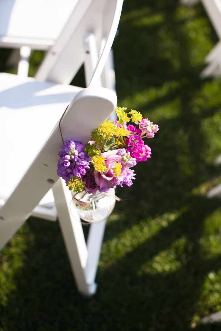 Purple, pink and yellow flower bouquets hung from ceremony chairs decorated the aisle with pops of color.