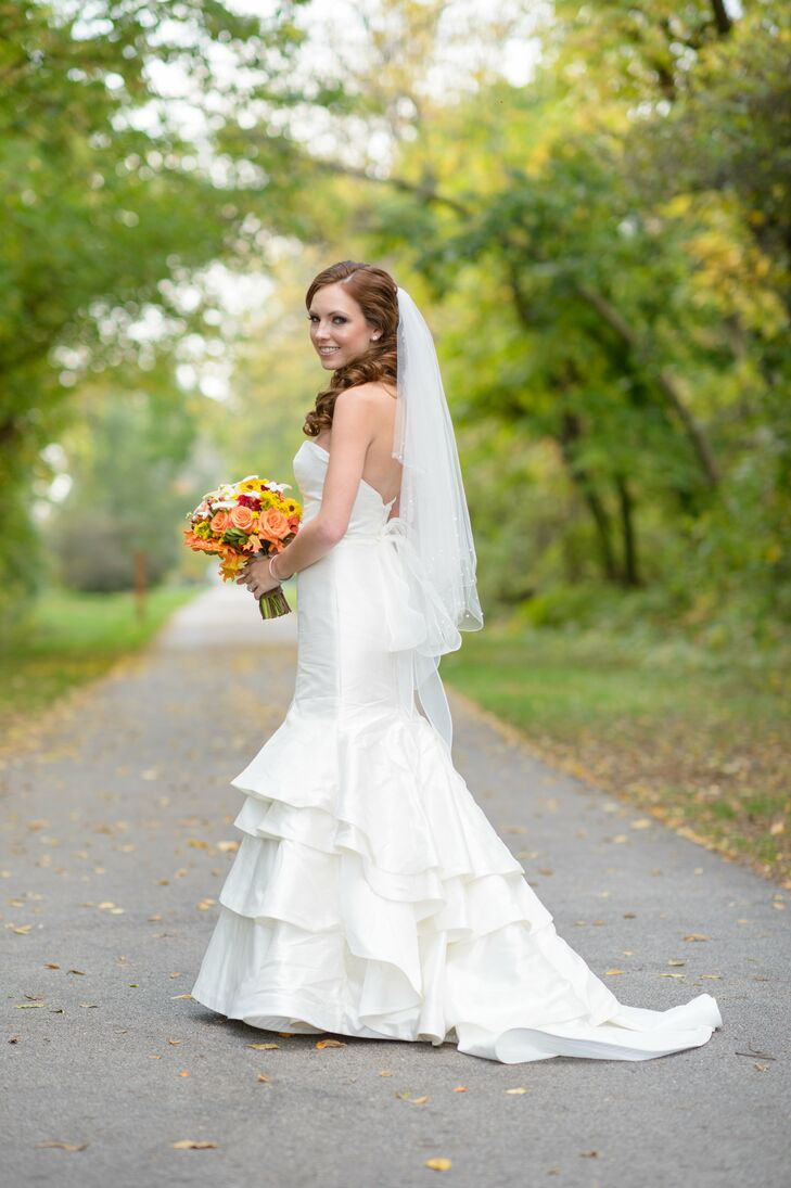 "Elysa wore a mermaid-style wedding dress with a ruffled skirt on her wedding day. She paired it with a fingertip veil. ""I wanted my dress to be unique but simple,"" she says."