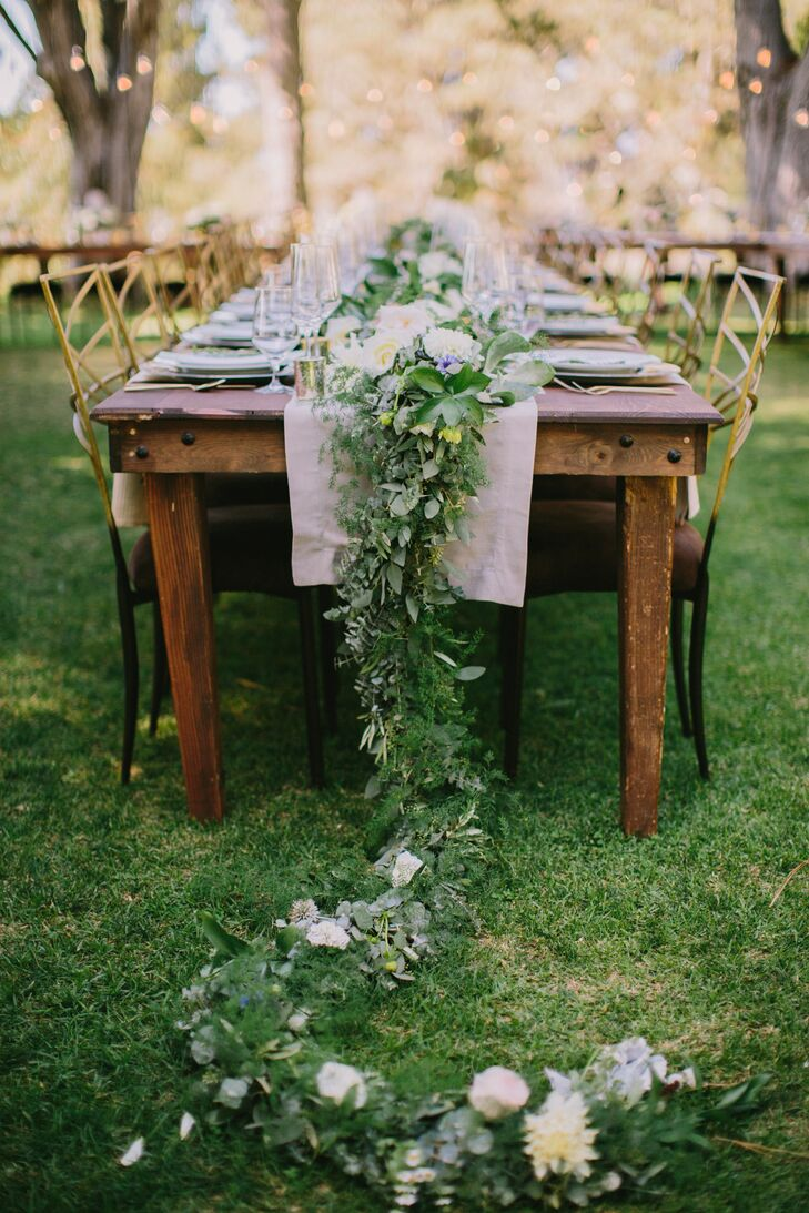 The long, wooden center table was topped with a lush garland of greenery, herbs and pops of white flowers.