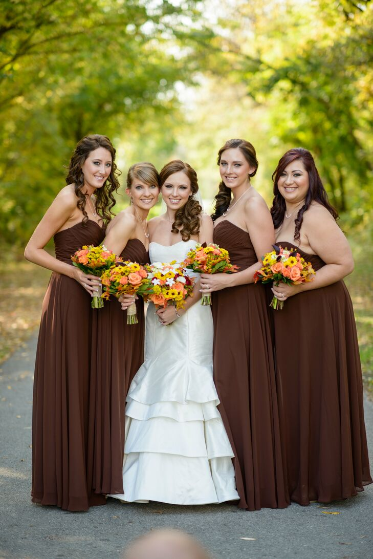 "Elysa's bridesmaids wore strapless, floor length dresses in brown by Jim Hjelm. ""I wanted everyone to be in a neutral fall color that would be flattering on everyone and complement our color scheme,"" Elysa says."