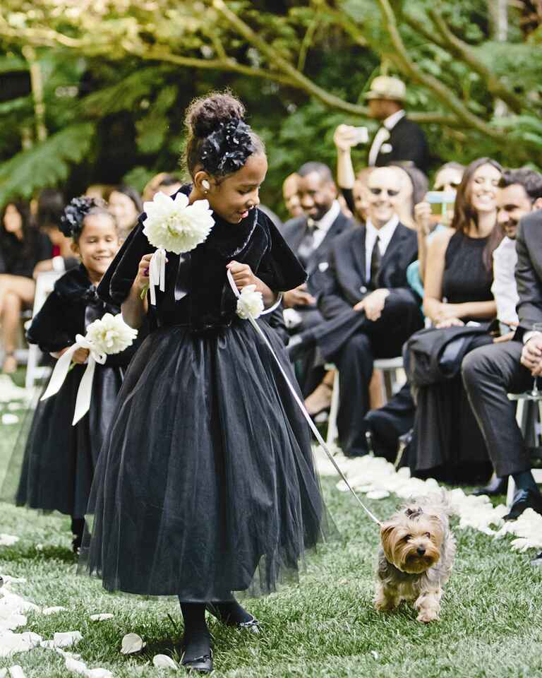 Glam flower girls with formal dresses and shawls walking a dog down the aisle