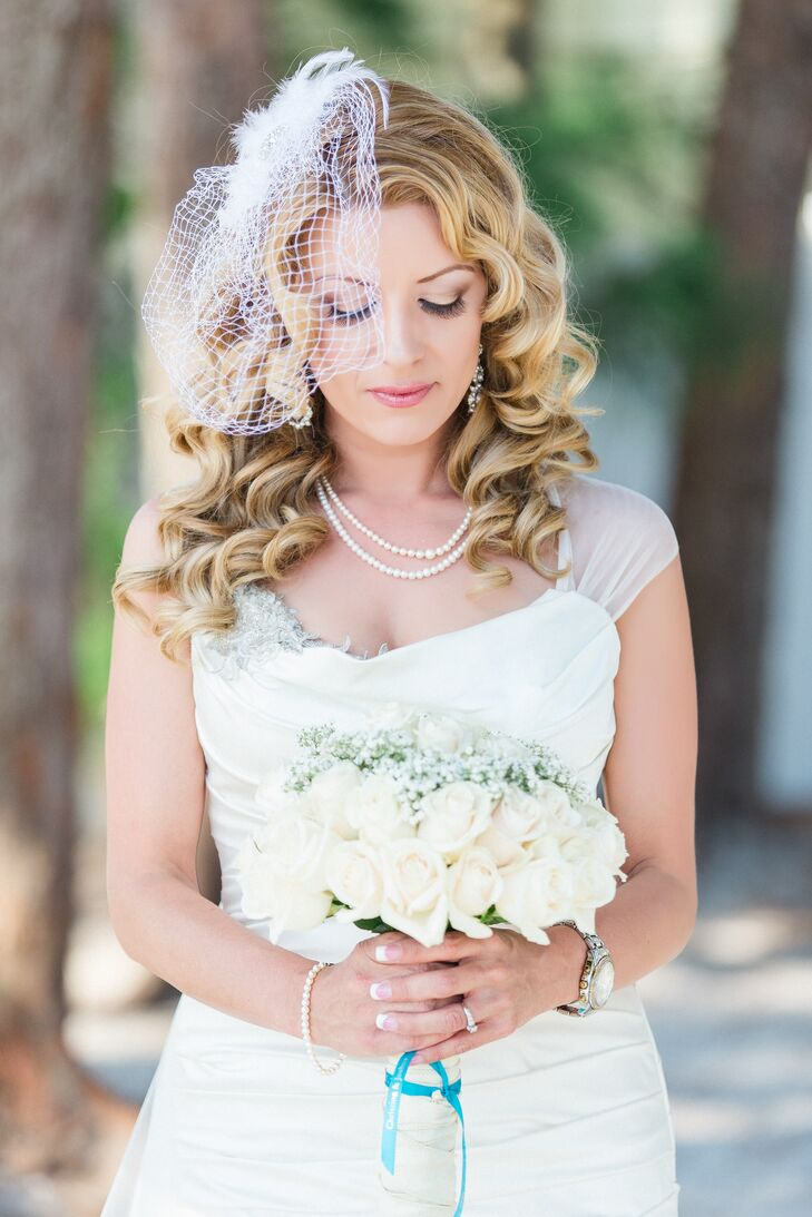 Amid a sea of color in their outdoor wedding, Christina stood out with all-white accessories. She carried a sweet arrangement of baby's breath and white roses up the aisle as a simple birdcage veil accented her curled hairstyle. For a twist, a bold white feather accented the headpiece.