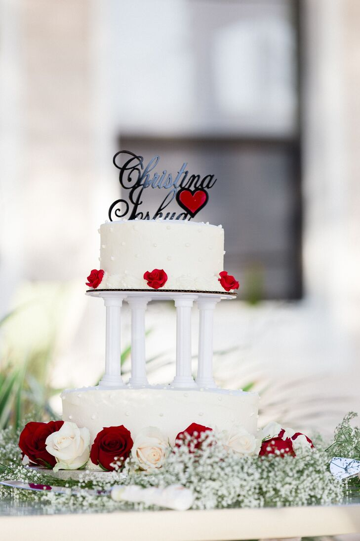The team at a local Publix bakery picked up on Christina and Josh's rose centerpieces with a classic touch. Each white tier was circled with red and white roses as a custom black topper tied the look together with a personal touch.
