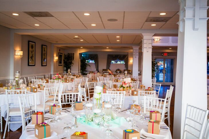 The dining room at Herrington on the Bay was decorated with white and mint green accents. The centerpieces varied by table, some with white roses in tall glass jars, and others an assortment of pink and orange roses mixed with dahlias and accented with moss.