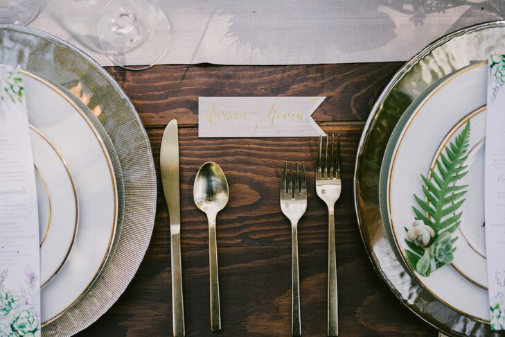 Tables were set with gold flatware and chargers, as well as napkins that had pops of gold. The colors were paired with vintage postcard-inspired menus and place cards, which also integrated gold-foil lettering.