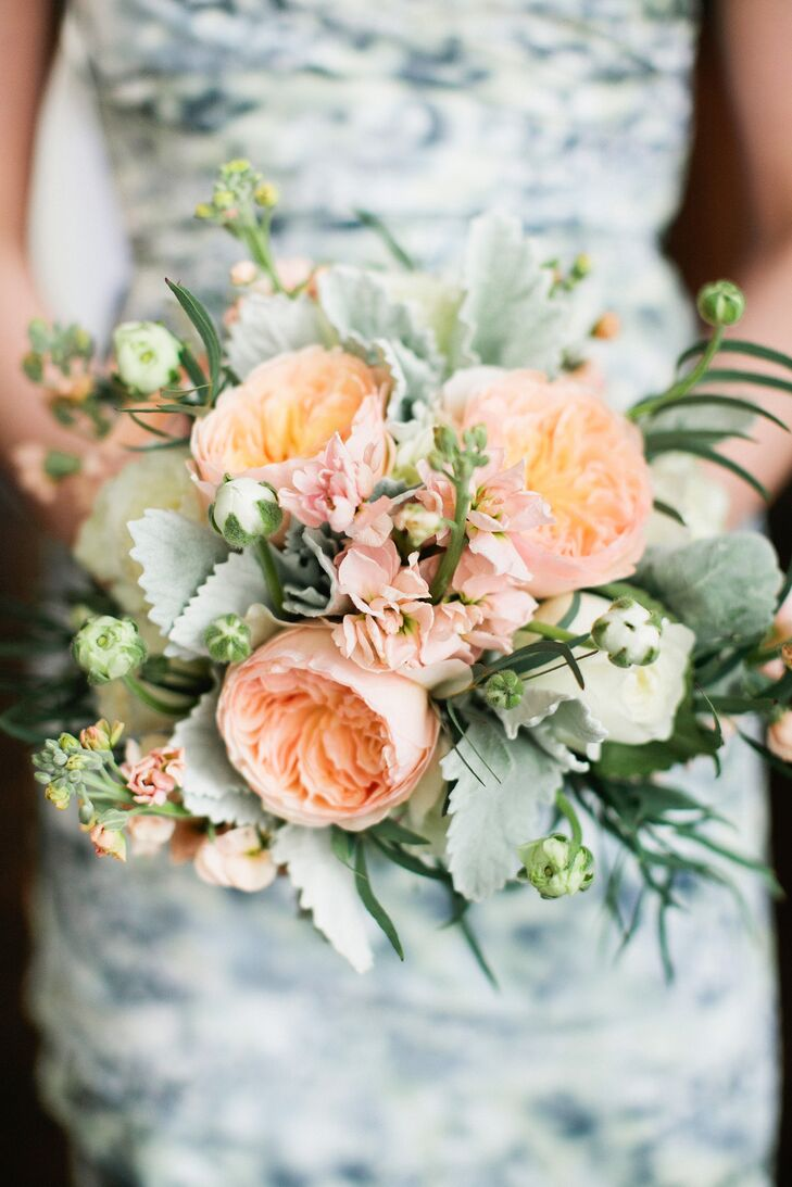 Nicole's maid of honor carried garden roses, stock and dusty miller in her textured peach and mint bouquet. The colors really popped against her printed, strapless cocktail-length blue patterned Monique Lhuillier dress.
