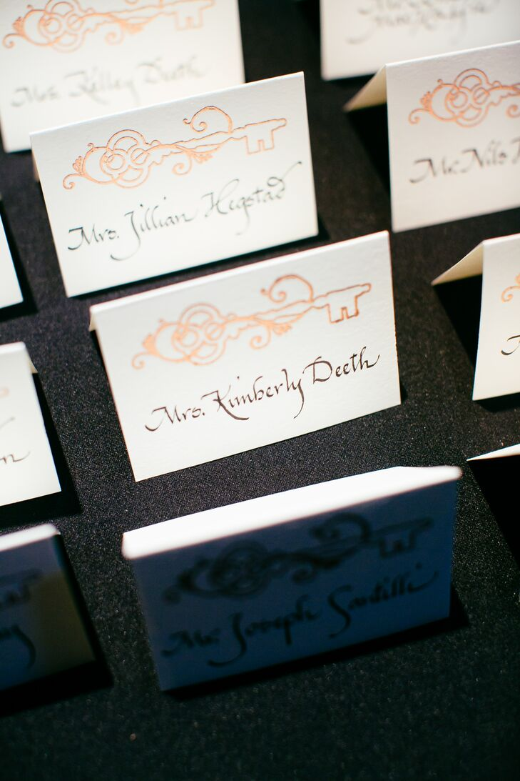 Wanting to incorporate the history of their venue (Boston jail-turned-hotel), the couple included an antique key motif on all the stationery. The escort cards were heat-embossed with the gold heat design, and the names were completed with black calligraphy.