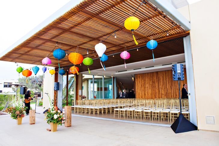 Colorful lanters hung from the ceiling at Scripps Seaside Forum in La Jolla, California. Rows of chiavari gold chairs faced where Suzanne and Chris were married.