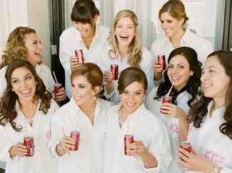 Bridesmaids drinking champagne in monogrammed getting ready shirts
