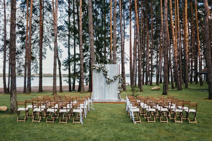 Katya and Nikita exchanged vows among the pines at Shishki Hotel in Zagorshchnya, Belarus, with a lake as their backdrop. Their altar was draped with blue fabric and embellished with blooms.