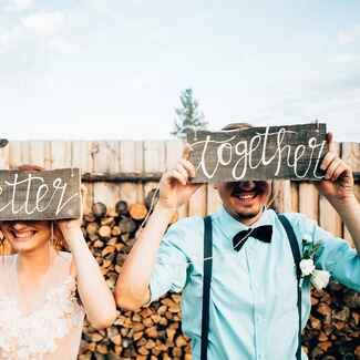 Bride and Groom Holding DIY Signs