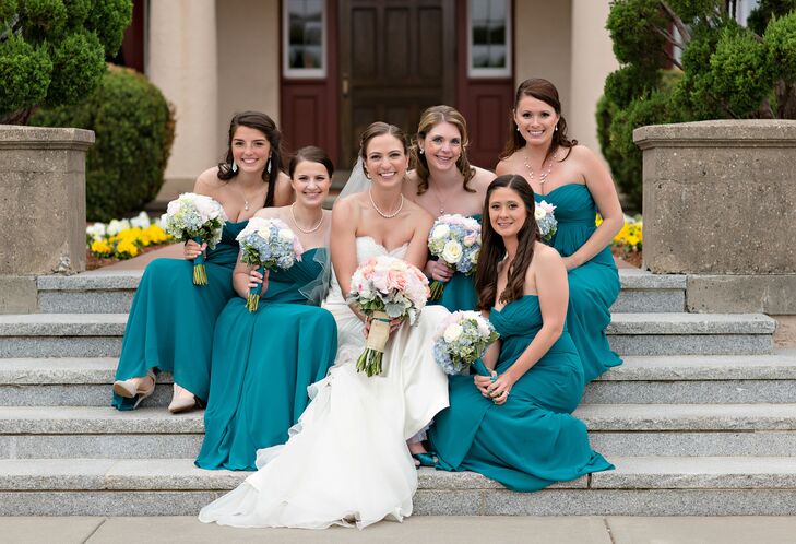 Lindsey played up the wedding's Cape Cod-inspired color palette by choosing a brilliant teal hue for her bridesmaids to wear down the aisle. The matching Bill Levkoff gowns complemented the strapless style of Lindsey's own, while the airy chiffon fabric kept the girls cool and comfortable. As a thank-you for all their support, Lindsey gave each of the bridesmaids sterling silver Cape Cod bracelets.