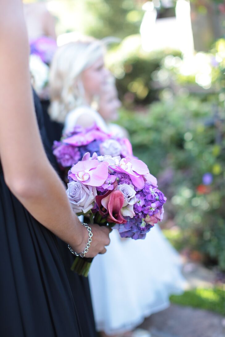 Kelly had always wanted black bridesmaid dresses with purple orchid flowers and incorporated the bright blooms throughout all of their arrangements.