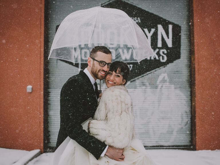 Winter wedding couple with umbrella in snow