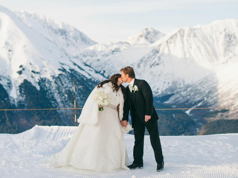 newlyweds kissing on a mountaintop in Alaska