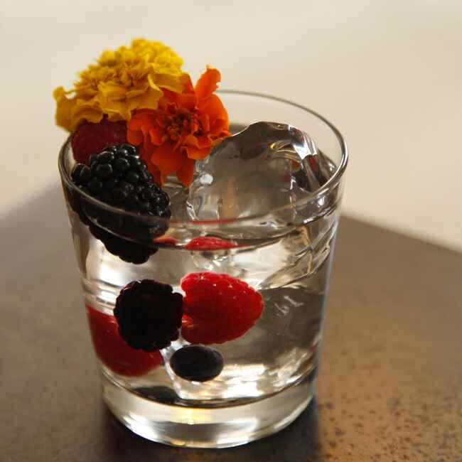 clear drink with berries and flowers