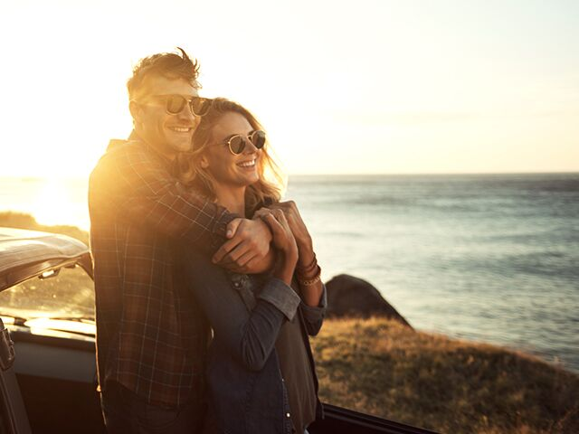 Couple enjoying scenic ocean views while standing against car.