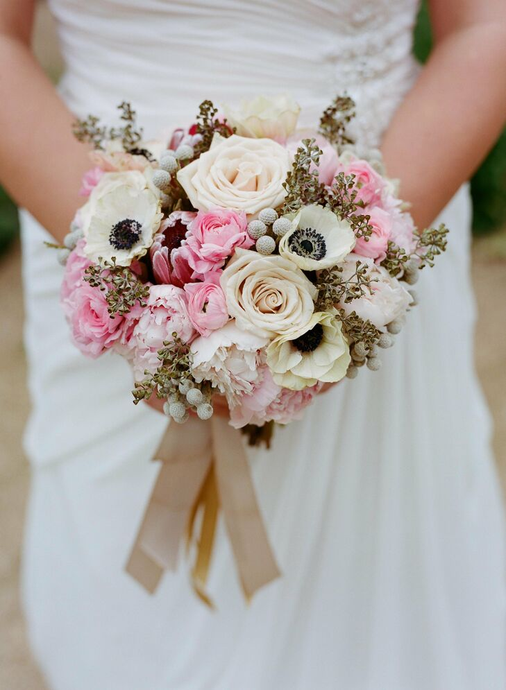 The bride carried a mix of ivory and pink roses, anemones, ranunculus and peonies tied with a gold ribbon.