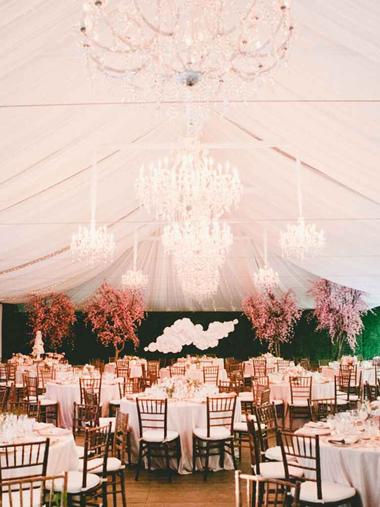 Outdoor tented wedding with chandeliers and cherry blossom trees