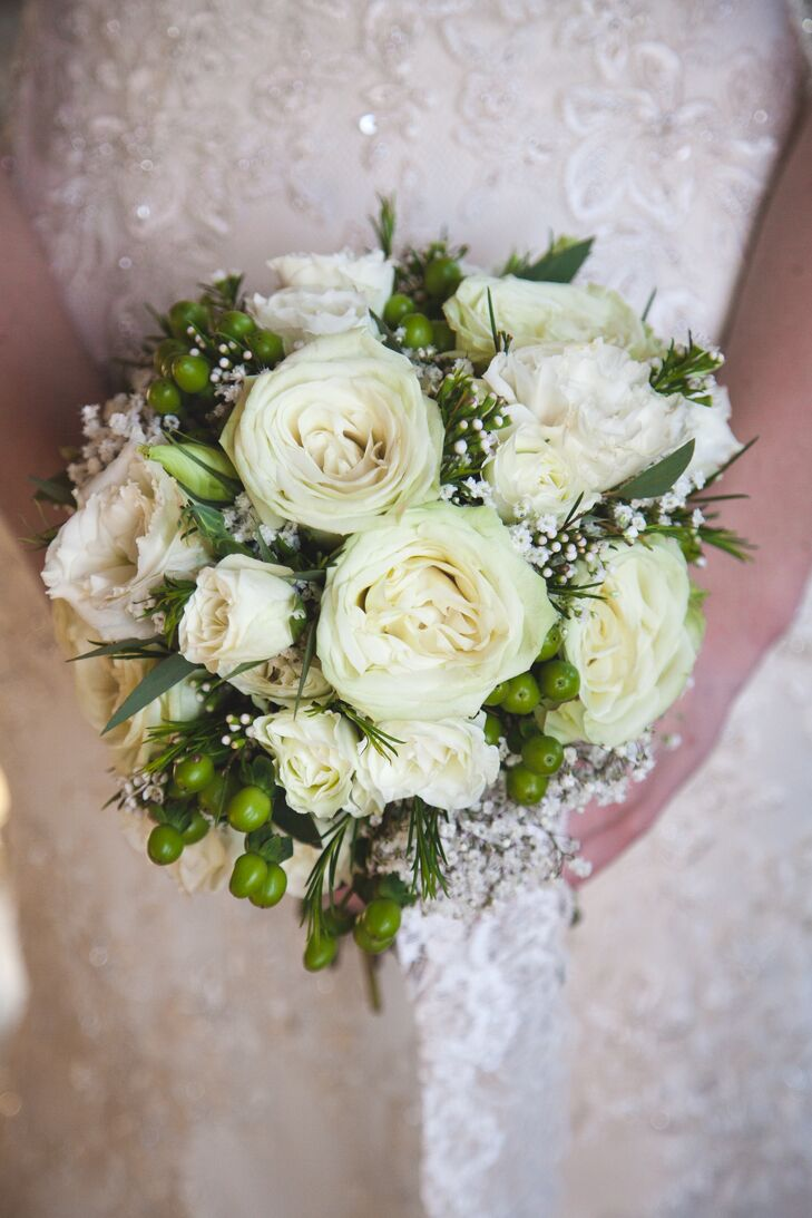 Kira carried white roses, baby's breath and hypericum berries in her white and green bouquet.