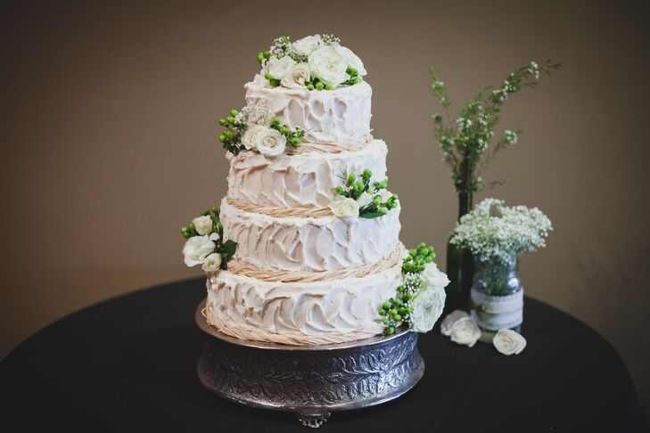 Kira and Kyle enjoyed a four-tier wedding blush buttercream wedding cake wrapped in twine and decorates with roses, baby's breath and hypericum berries.