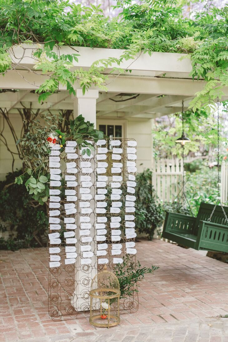 Guests located their seats through the white escort tags  displayed on an iron board posted on a white pillar, which was surrounded by lush green landscaping on the property.