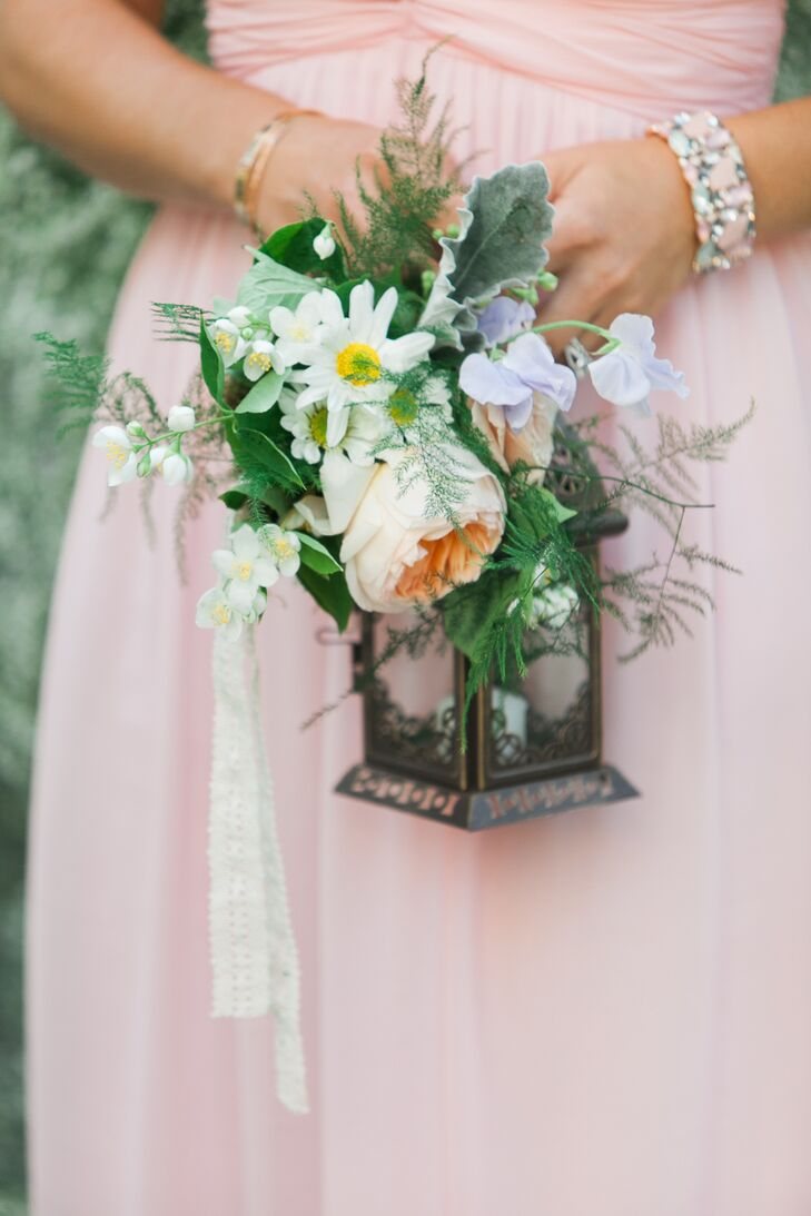 Instead of the traditional bouquet of blooms, Ashley's bridesmaids carried antique lanterns adorned with cascades of garden roses, sweet peas, daisies and maidenhair ferns.