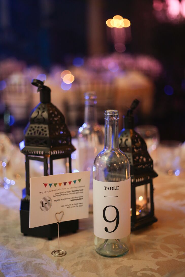 Instead of using flowers throughout the reception decor, the bride chose black candleholders and clear glass bottles as the focal point for each table.