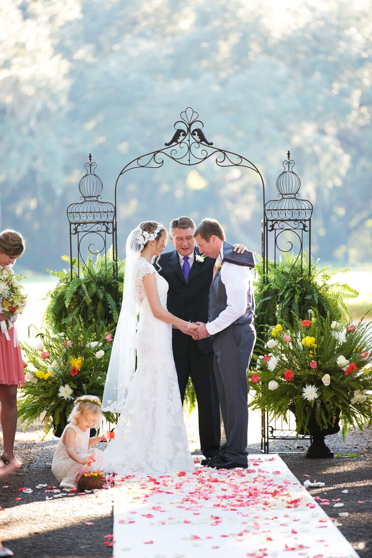 A wrought iron gate surrounded by green ferns served as a backdrop for the outdoor ceremony.