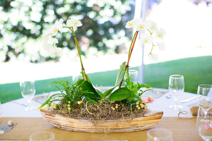 Some tables were decorated with whitewashed boats filled with phalaenopsis orchids, button ferns, autumn ferns and burlap accents, while other tables had vintage lanterns, beachwood, baby's breath and candles surrounded by flowers.