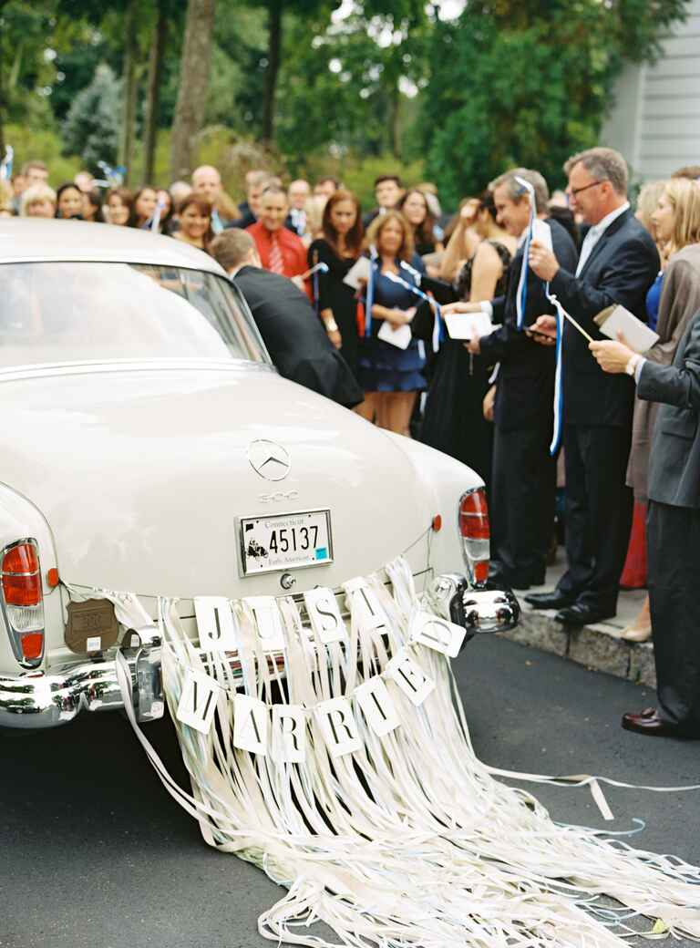 """Just Married"" sign and streamers on ceremony transportation"
