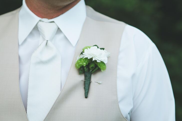 The groom had on a white buttoned up shirt with a khaki vest and pants. He wore he sleeves rolled, without a jacket, and completed the look with a white tie to match the bride.
